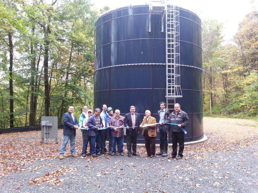 people cutting a ribbon in front of a water tank.